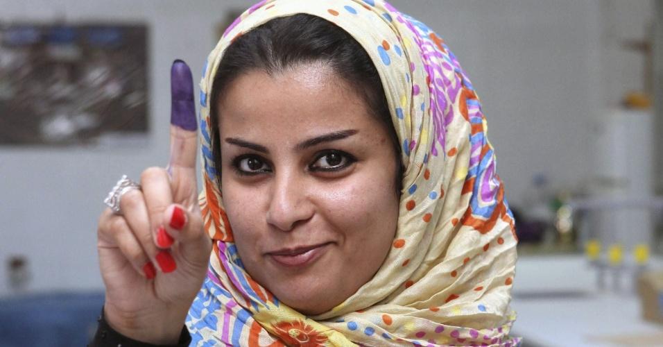 7.jul.2012 - Mulher mostra o dedo manchado de tinta após voltar no pleito que elegerá membros de cargos legislativos na Líbia