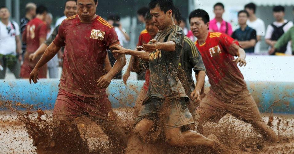 Jogadores disputam a bola em um torneio de futebol na lama disputado na China; 32 times com seis atletas cada disputam a competição, que dá uma tocha comemorativa dos Jogos de Londres como prêmio