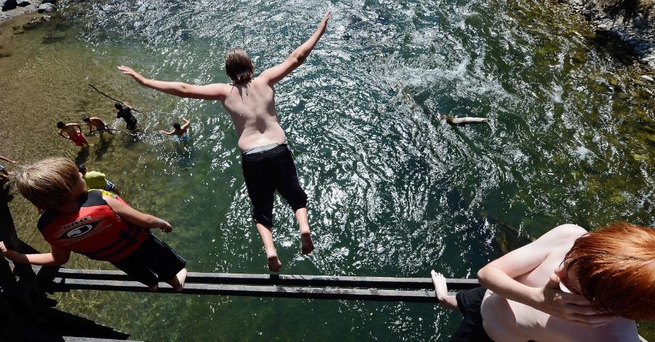9.jul.2012 - Garoto pula no rio Big Wood, em Sun Valley, nos Estados Unidos; relatório do serviço nacional Oceânico e Atmosférico dos EUA aponta que, nas áreas mais centrais do país, o mês de junho foi o mais quente desde que começaram as medições, em 1985