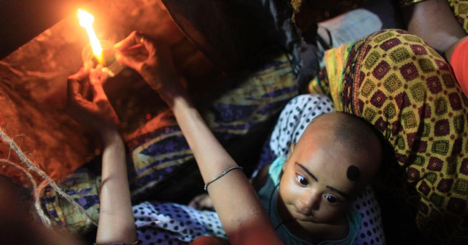 10.jul.2012 - Com o filho no colo, mulher trabalha com vidro em fábrica de pulseiras em Old Dhaka, Bangladesh. Segundo a gerência da fábrica, cerca de 150 mulheres e crianças trabalham 15 horas por dia, por um salário de US$ 6 a US$ 8 por semana