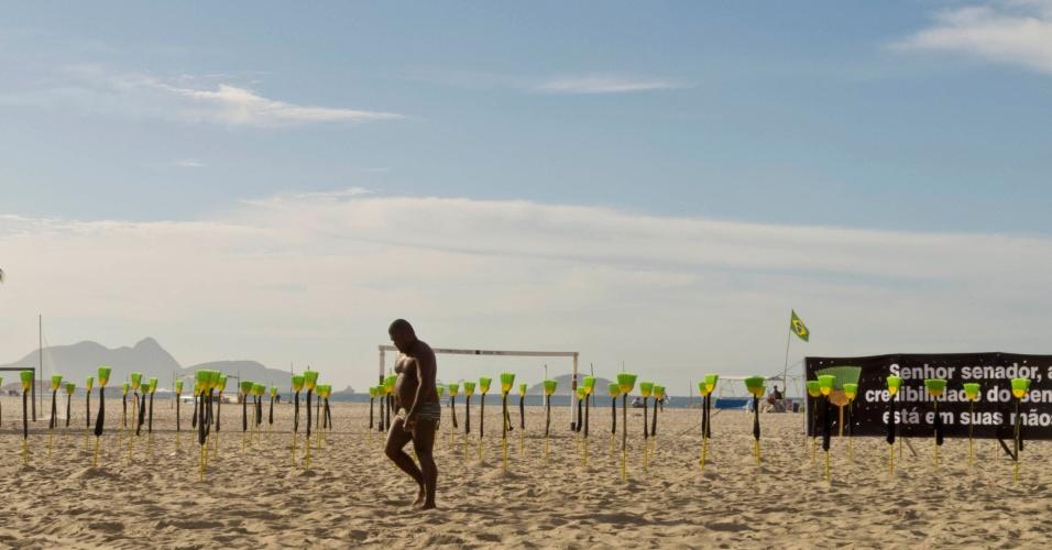 10.jul.2012 - Homem caminha em frente de vassouras com gravatas enterradas nas areias da praia de Copacabana, no Rio de Janeiro, durante ato contra a corrupção no Senado, organizado pela ONG Rio de Paz