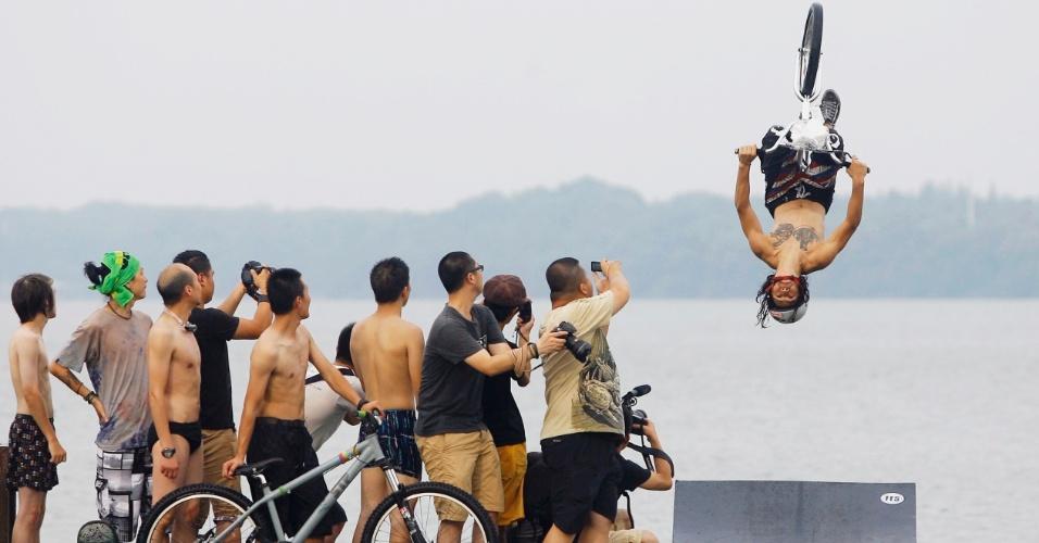 10.jul.2012 - Pessoas observam praticante de uma modalidade de ciclismo em que deve-se pegar uma rampa, fazer a manobra e cair no lago em Wuhan, na China