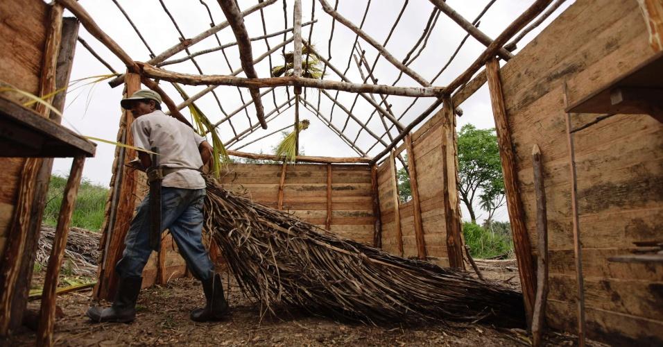 10.jul.2012 - Trabalhador migrante separa material para o telhado de uma casa em programa de construção habitacional do Estado, na periferia de Havana, em foto do dia 25 de junho