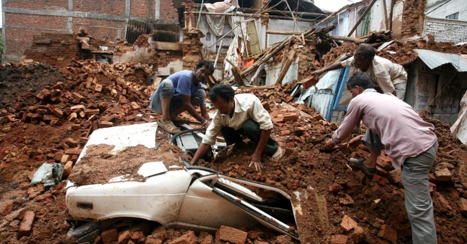 10.jul.2012 - Várias pessoas cavaram um veículo após um prédio de três andares desabar em Bhopal, Madhya Pradesh (Índia)