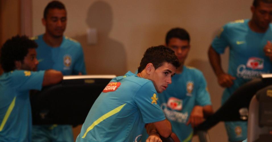 Oscar descansa enquanto companheiros de seleção realizam treino de corrida na academia do hotel no Rio de Janeiro