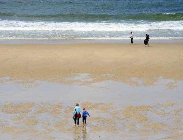 Turistas caminham pela praia Lacanau, na França (10/07/2012)