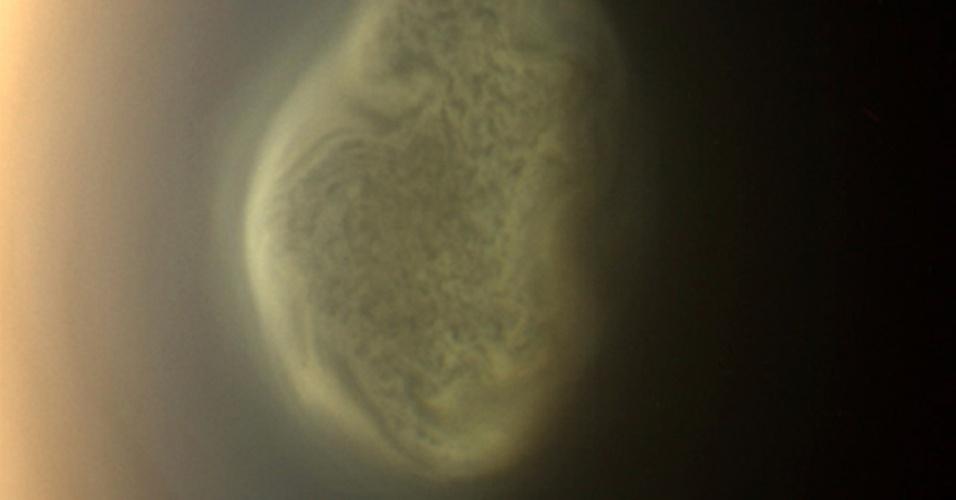 11.jul.2012 - A cor verdadeira de um redemoinho no polo sul da lua Titã, de Saturno, é registrada pela sonda Cassini, da Nasa. A captura da imagem foi feita pouco antes de um sobrevoo realizado no mês passado. O polo sul de Titã tem mais de 5.000 km de diâmetro e o redemoinho pode ter relação com o inverno. O registro só foi possível por causa da órbita inclinada da sonda