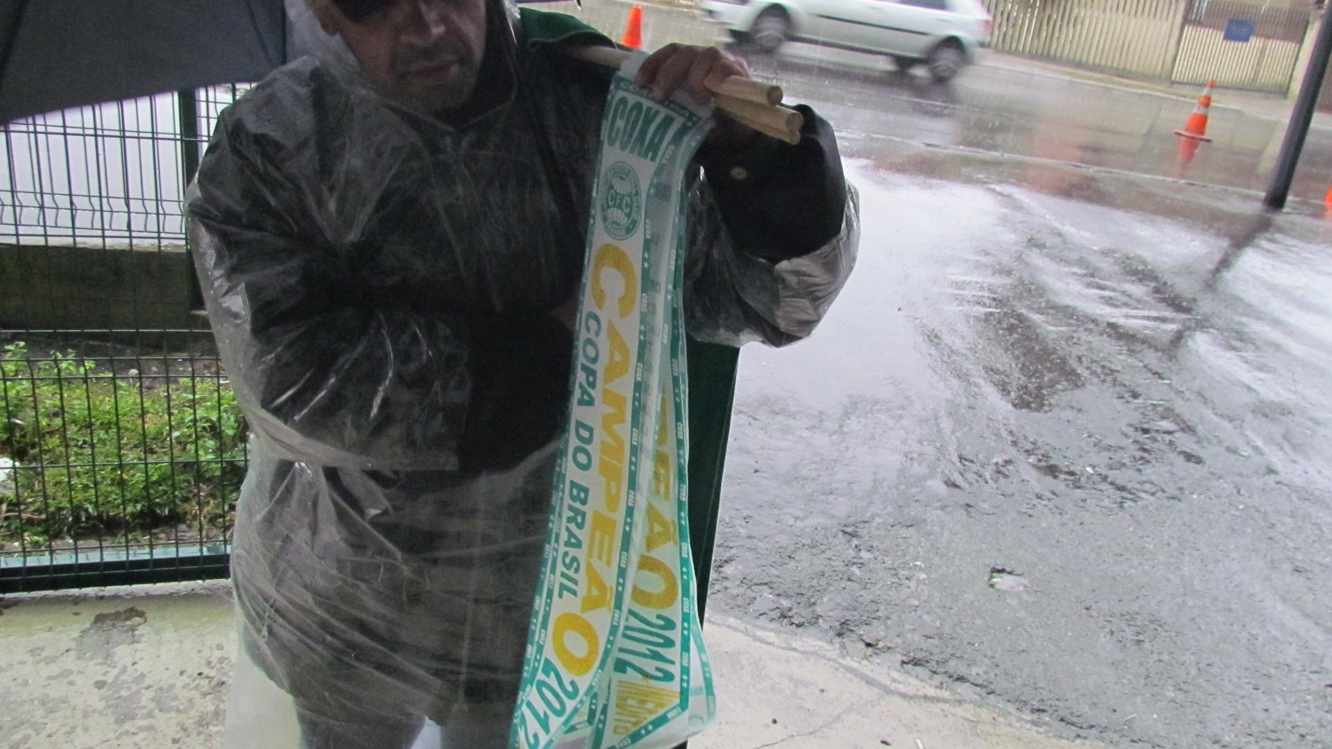 Protegido da chuva, vendedor oferece faixas de campeão do Coritiba