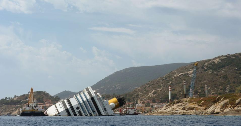 12.jul.2012 - Equipe trabalha na remoção do navio de cruzeiro Costa Concórdia na quinta-feira (12), próximo à ilha de Giglio, na costa da Itália. Os trabalhos de remoção começam seis meses depois do acidente que deixou a embarcação atracada no local