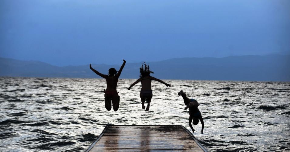 12.jul.2012- Garotas pulam de pier para nadar no lago Ohrid, na Macedônia