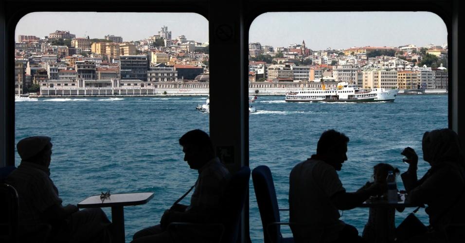 12.jul.2012- Silhuetas de pessoas conversando sentadas em mesas dentro de balsa, em Istambul, na Turquia