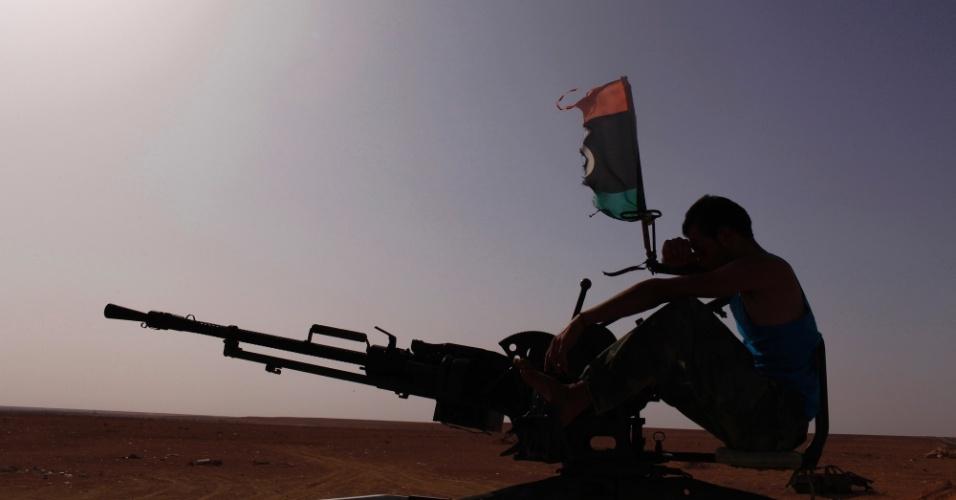 12.jul.2012-Integrante de uma milícia testa sua arma perto da base militar de Bir Doufan, na Líbia, nesta quinta-feira (12). O país ainda apura o resultado das eleições parlamentares do sábado (7)