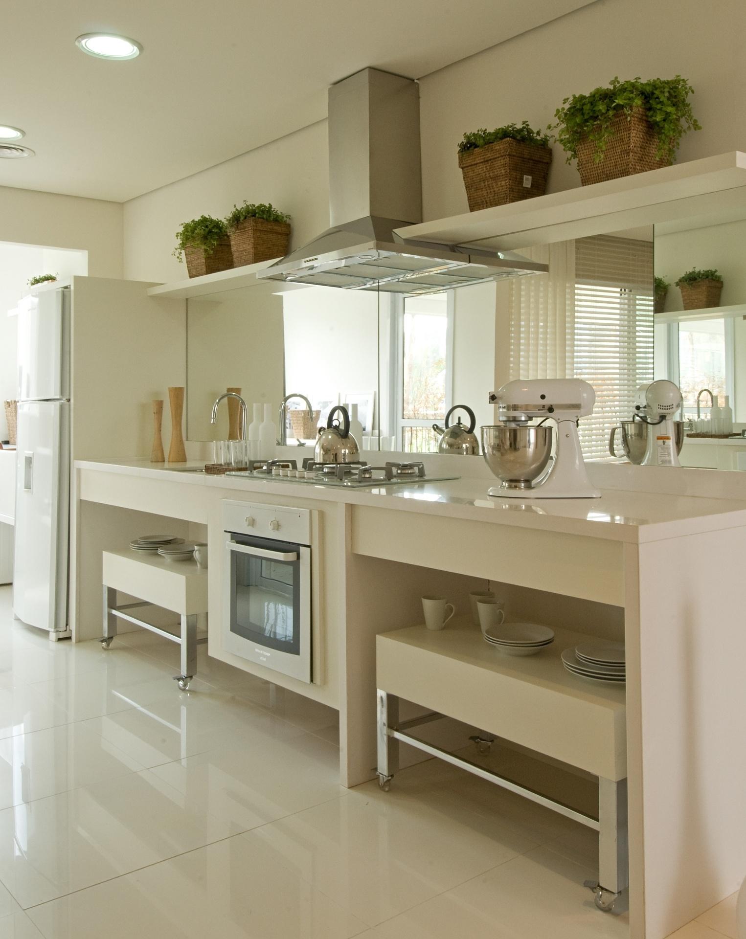 Na cozinha integrada, elaborada pela arquiteta Débora Aguiar, o único contraste fica por conta da coifa, dos metais e dos pés das mesinhas embutidas sob o móvel. O branco passa a assepsia desejada em uma cozinha