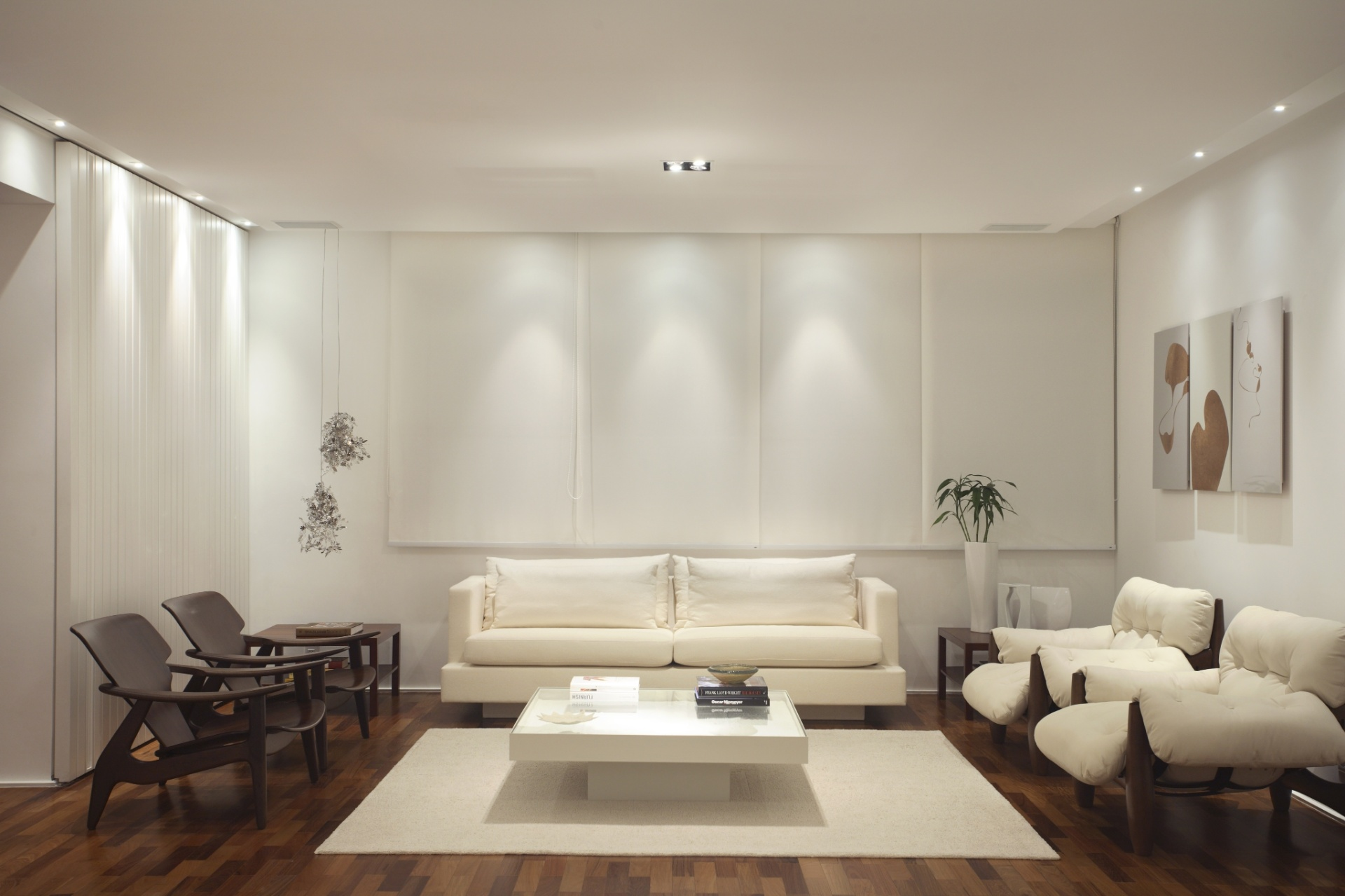 Na proposta da arquiteta Carla Dichy para a sala de 30 m², o branco não só ampliou o ambiente assim como possibilitou o jogo de contrastes com a madeira e os tons neutros. A arquiteta compôs com as curvas das poltronas assinadas por Sérgio Rodrigues e as linhas retas dos sofás e mesas