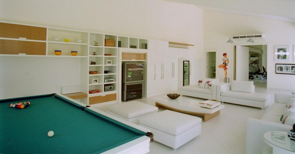 Na sala de jogos, a arquiteta Jóia Bergamo usou o branco para destacar a sensação de amplitude. O verde do feltro da mesa de jogos surge gritante em meio ao mobiliário laqueado. Já o carvalho americano em detalhes e os estofados de couro da Breton levam aconchego ao ambiente