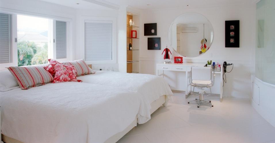 Nesta suíte de uma casa de praia, a arquiteta Jóia Bergamo evitou limitar-se ao branco, usado no piso, paredes e no mobiliário revestido em laca, pincelando tons de vermelho e rosa nas almofadas e em detalhes da decoração