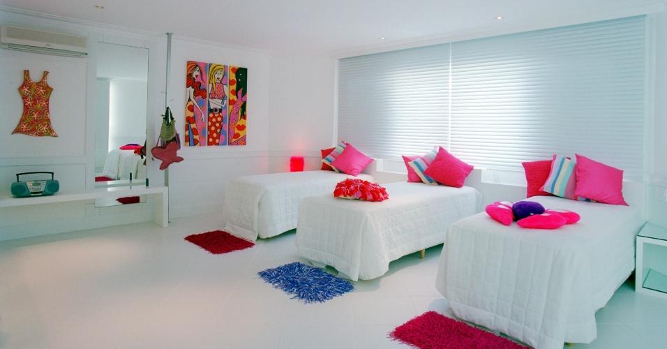 No quarto das filhas de uma casa de praia, a arquiteta Jóia Bergamo repetiu a mesma solução da suíte dos pais: para quebrar com o branco, ela espalhou quadros, tapetes e almofadas coloridas