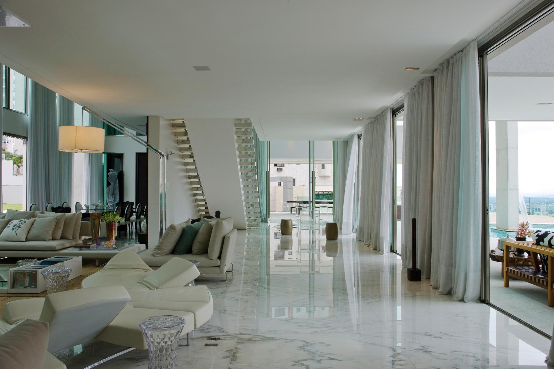 O living com 200 m² de área ficou bem mais amplo no projeto da arquiteta Myrna Porcaro graças ao piso em mármore, vidro, e parede e cortinas brancas. O sofá off-white e o mobiliário em tom neutro unificam os ambientes