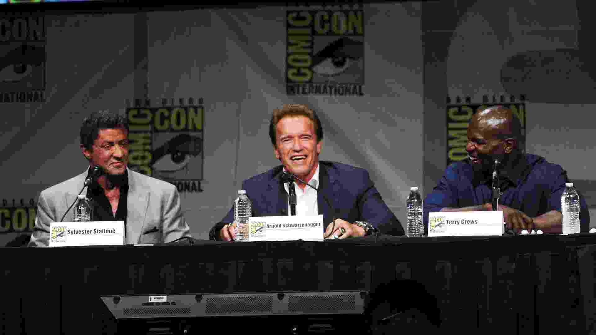 """Sylvester Stallone, Arnold Schwarzenegger e Terry Crews durante o painel de """"Os Mercenários 2"""" (13/7/12) - Getty Images"""
