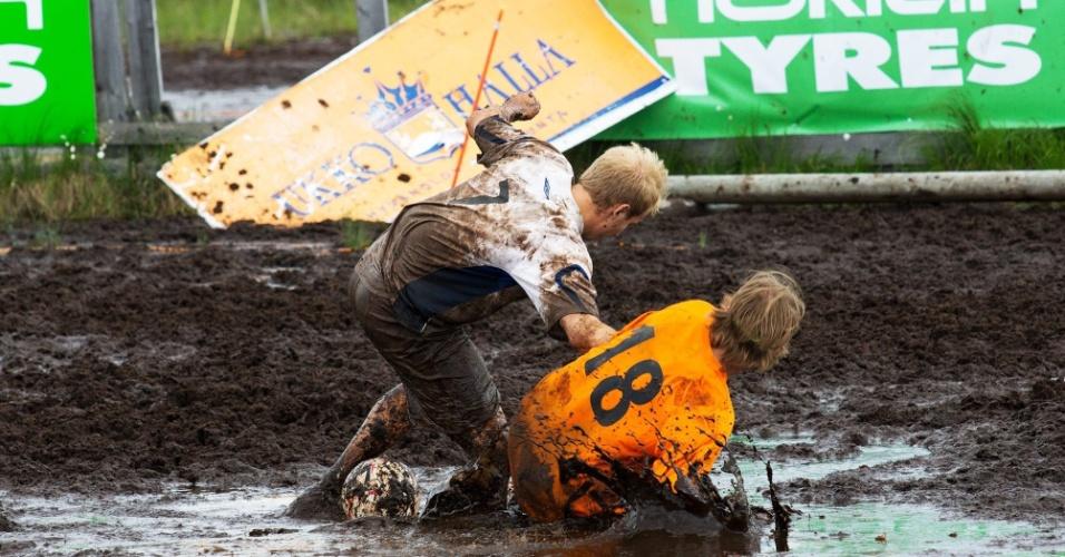 Durante final do Campeonato Mundial de Futebol na lama, jogadores finlandeses disputam bola. O Telinekataja bateu o FC Lerssi e conquistou o torneio, em Hyrynsalmi