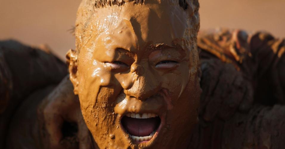 Competidor de um campeonato de futebol na lama em Pequim, na China, celebra vitória de sua equipe