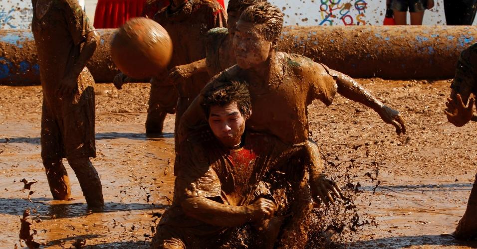 Jogadores chineses, em Pequim, disputam campeonato de futebol na lama