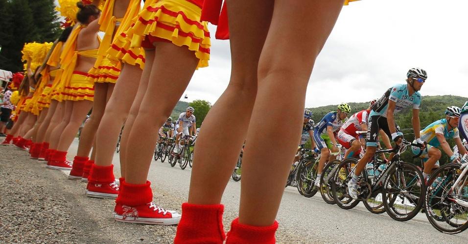 Pelotão de ciclistas passa por cheerleaders na décima quarta etapa da Volta da França