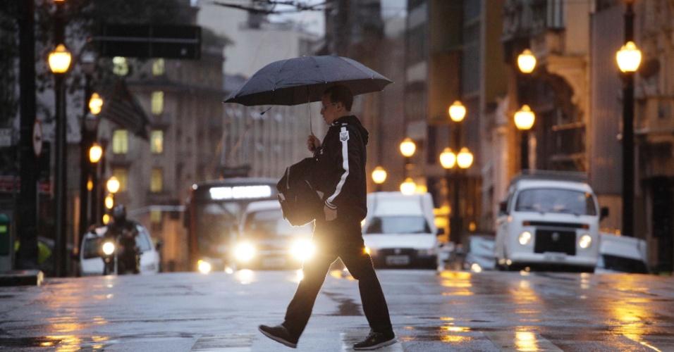16.jul.2012 - Rapaz se protege da chuva e do frio que atingem a região central de São Paulo na manhã desta segunda-feira (16). A média de temperatura previsa para hoje na capital paulista não ultrapassa dos 15ºC