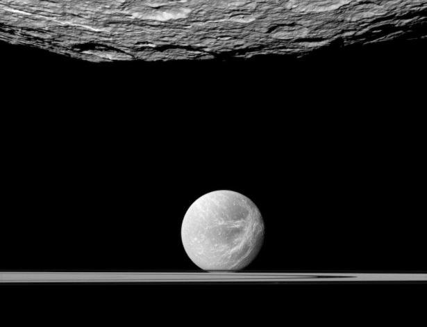 16.jul.2012 - Fotografia cedida pela Nasa mostra a lua Réa, de Saturno, com suas crateras, e a lua Dione, sobre os anéis do planeta. O registro foi feito pelas lentes da sonda Cassini a una distância aproximada de 61 mil quiolômetros de Réa