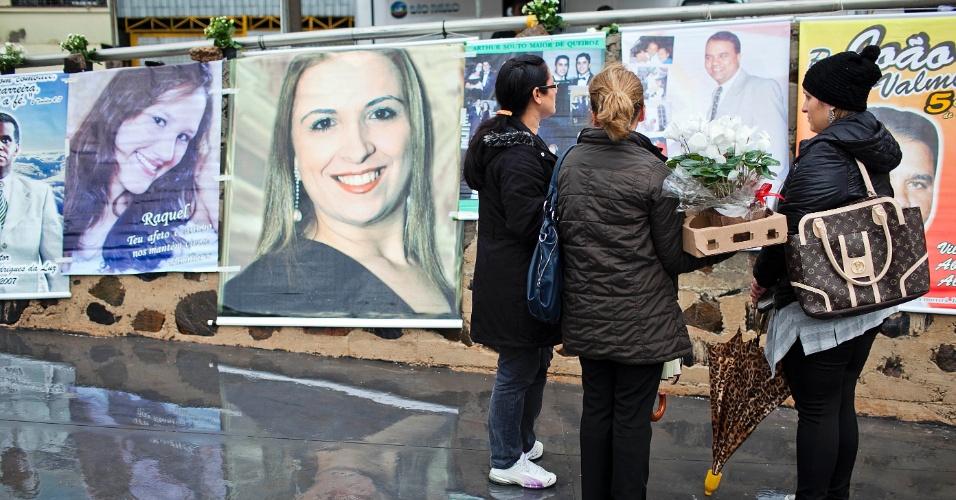 17.jul.2012 - Grupo observa fotos das vítimas do acidente da TAM, momentos antes da inauguração da praça batizada de Memorial 17 de Julho, localizada na avenida Washington Luiz, na zona sul de São Paulo. Em 2007,  o Airbus 320 da empresa se chocou contra um prédio da mesma companhia e deixou 199 mortos