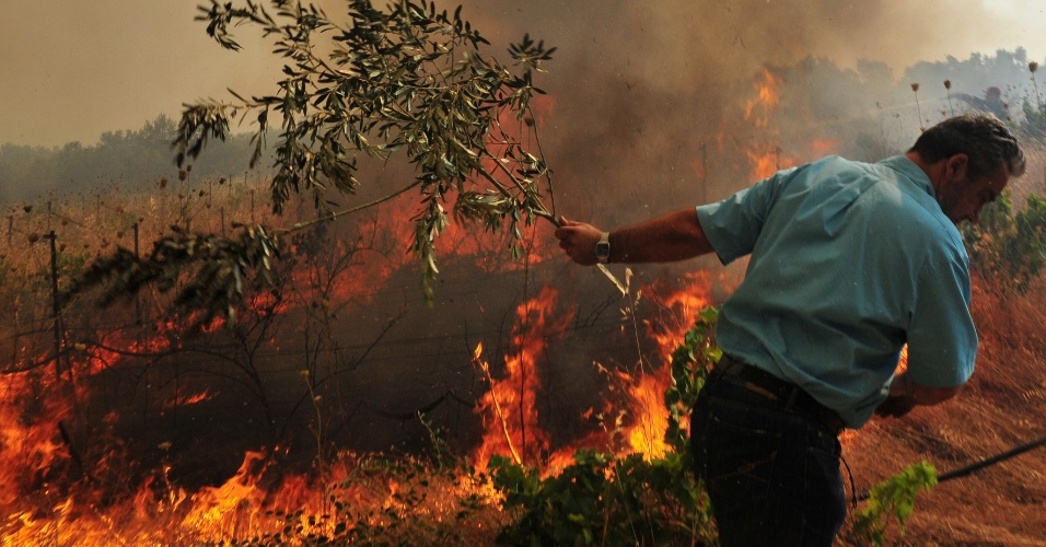 17.jul.2012 - Morador tenta conter incêndio que atingiu parte das montanhas de Spathovouni, em Corinto (Grécia). O fogo se expandiu devido aos fortes ventos
