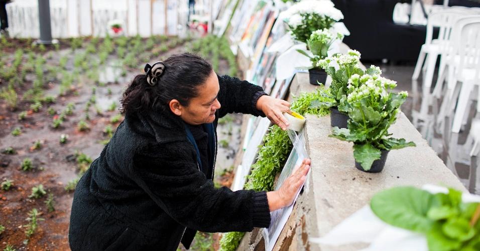 17.jul.2012 - Mulher coloca foto de uma das vítimas do acidente da TAM em local da praça Memorial 17 de Julho, que será inaugurada, nesta terça-feira, na zona sul de São Paulo. Em 2007, o Airbus 320 da empresa se chocou contra um prédio da mesma companhia e deixou 199 mortos