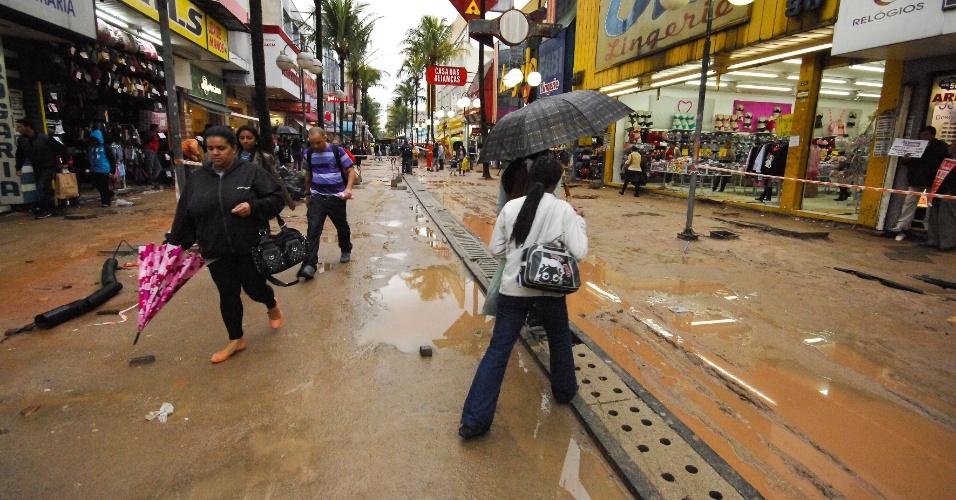 17.jul.2012 - Após forte chuva, pedestres enfrentam lama  na rua Antônio Agu, em Osasco (SP), que está com obras na via. O local é o principal centro comercial da cidade paulista