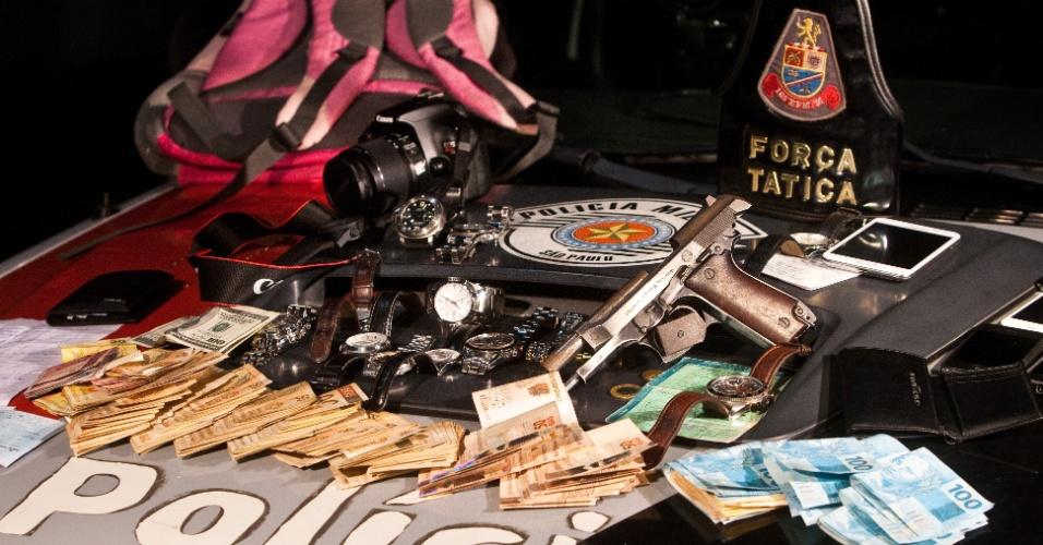 """17.jul.2012 - Suspeitos de praticar sequestro relâmpago e """"saidinha de banco"""" foram presos em uma favela na região da Vila Sônia, na zona oeste de São Paulo, na noite de segunda-feira (16). Foram apreendidos com eles cerca de R$ 11 mil, relógios, celulares, câmera fotográfica, cartões bancários, cheques e uma pistola 7.65. Duas motos utilizadas pelos suspeitos para fugir após os roubos também foram apreendidas"""