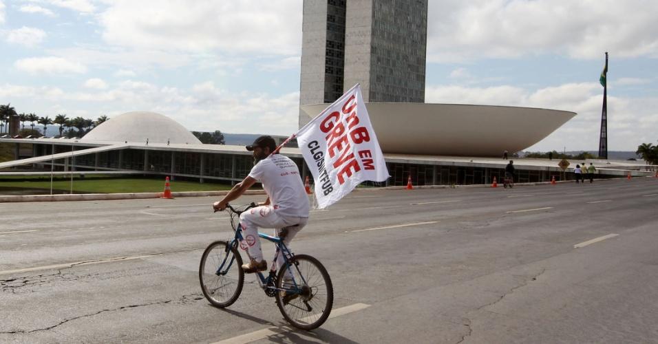 18.jul.2012 - Homem anda de bicicleta pelo Ministério do Planalto, em Brasília, com faixa da greve da UnB (Universidade de Brasília) durante a Marcha dos Servidores Públicos. A categoria reivindica reajustes salariais ao funcionalismo público