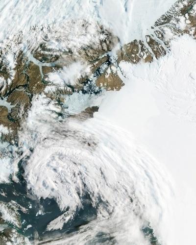 18.jul.2012 - A imagem, divulgada pela Nasa (agência espacial americana), mostra a geleira de Petermann deslizando em direção ao mar ao longo da costa da Groenlândia. Como outras geleiras grandes que terminam no oceano, pedaços de gelo se rompem da geleira de Petermann