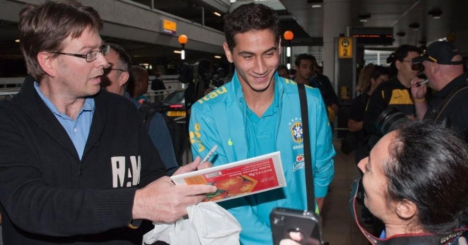 Paulo Henrique Ganso atende fãs no desebarque da seleção brasileira de futebol em Londres (17/07)