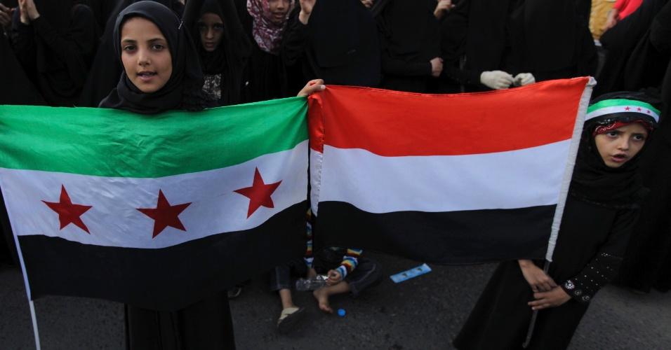 19.jul.2012 - Meninas carregam bandeiras do Iêmen e da Síria durante protesto do lado de fora da residência do presidente iemenita, Abd-Rabbu Mansour Hadi, em Sanaa, para exigir a demissão de todos os membros da família do ex-presidente Ali Abdullah Saleh