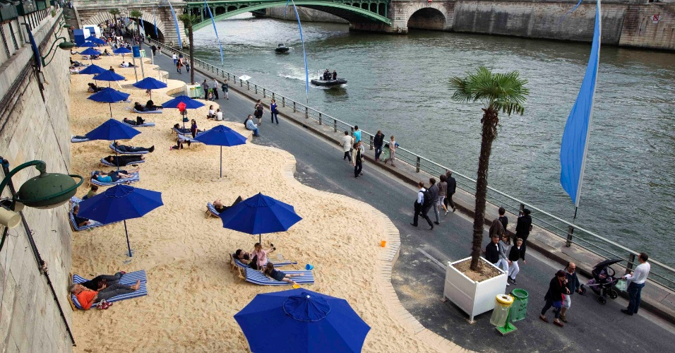 20.jul.2012 - Franceses e turistas curtem o sol em praia artificial construída ao longo das margens do Rio Sena, em Paris