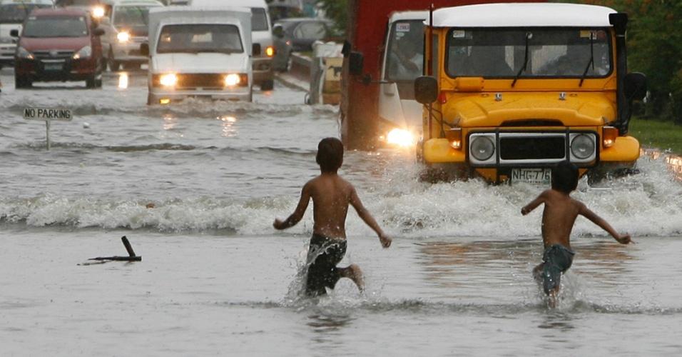 21.jul.2012 - Crianças brincam em rua inundada pelas fortes chuvas que castigam as Filipinas neste sábado (21), em Manila