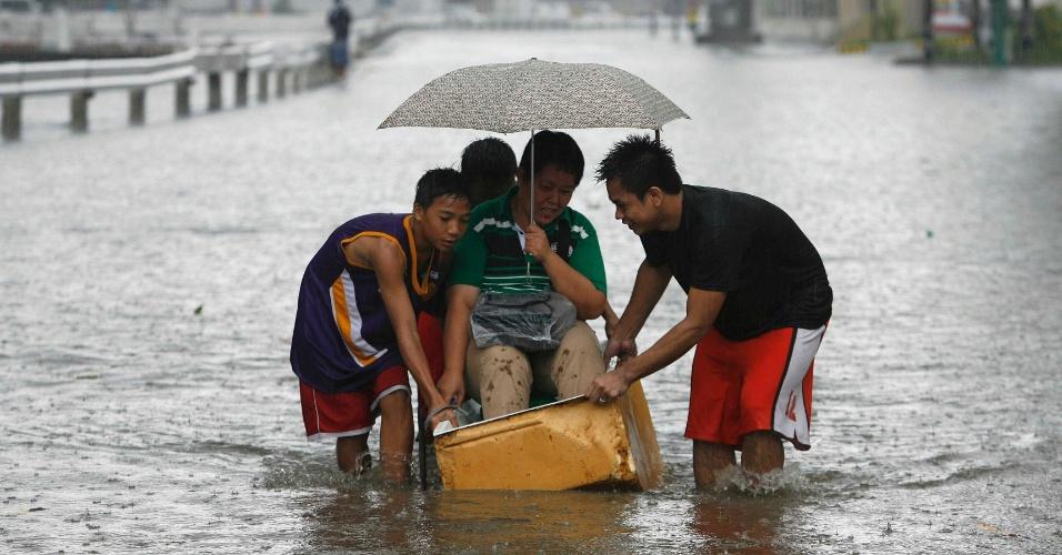 """21.jul.2012 - Filipinos empurram homem em um barco improvisado pelas ruas inundadas de Manila, neste sábado. As chuvas foram provocadas pela tempestade tropical """"Ferdie"""""""