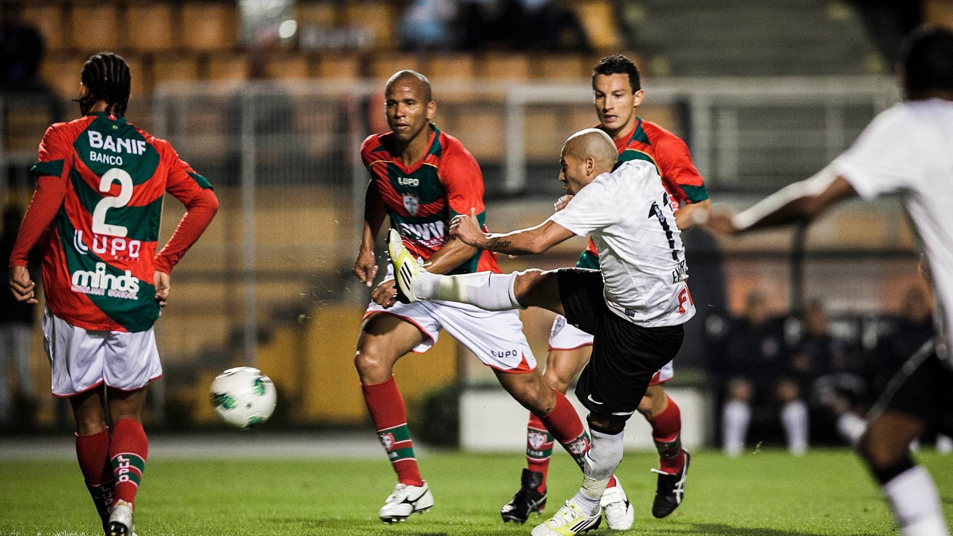 Atacante corintiano Emerson tenta o chute entre zagueiros da Portuguesa