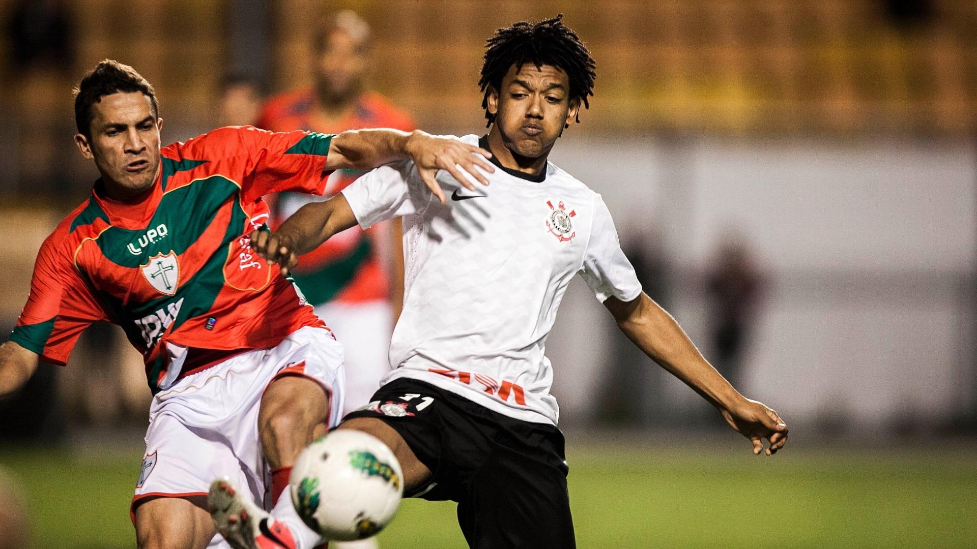 Atacante do Corinthians Romarinho (d) disputa a bola com adversário da Portuguesa