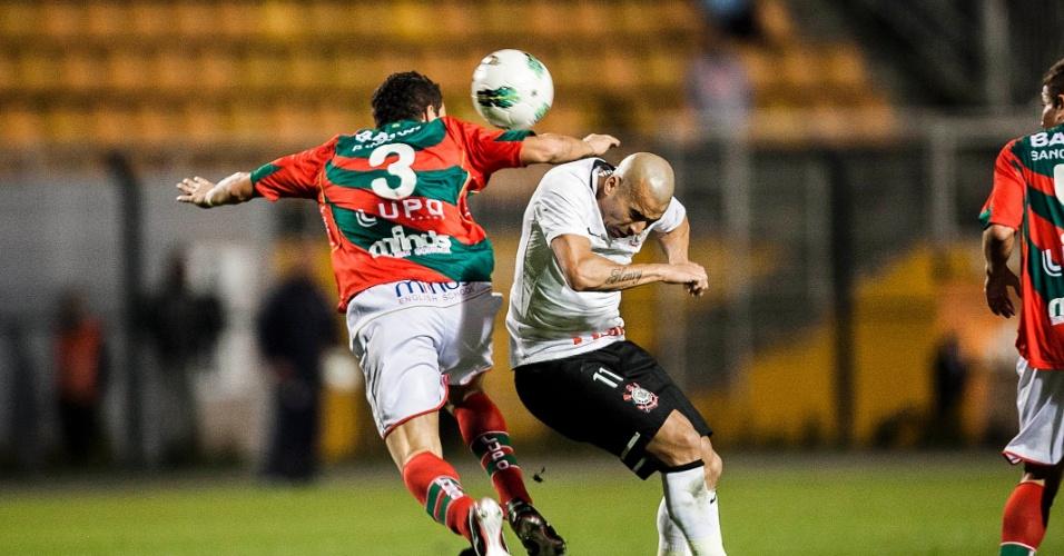 Corintiano Emerson (d) disputa a bola com zagueiro da Portuguesa Gustavo