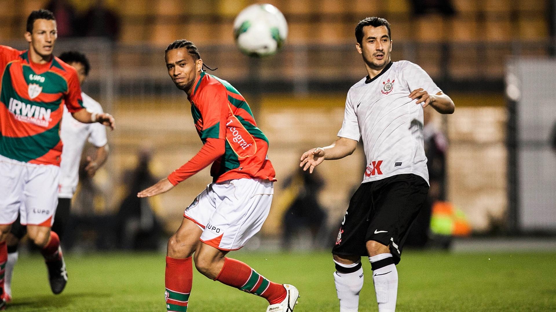 Meia corintiano Douglas (d) disputa jogada durante partida contra a Portuguesa no Pacaembu