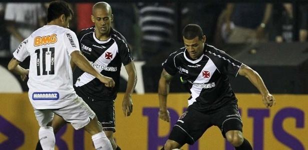 Volante do Vasco Nilton (d) tenta proteger a bola sob a marcação do santista Felipe Anderson