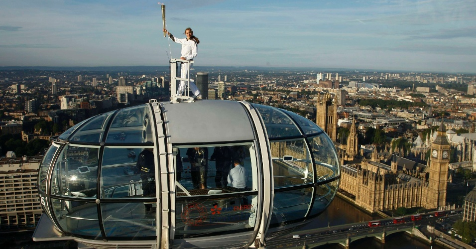 22.jul.2012 - A exploradora Amelia Hempleman-Adams, 17, ergue a tocha olímpica do alto de uma cápsula no London Eye (roda-gigante situada no rioThames), em Londres (Inglaterra), neste domingo (22)