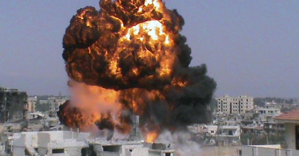 22.jul.2012 - Fogo é visto ao redor de edifícios após a explosão de uma bomba em Damasco, na Síria, neste domingo. Os confrontos na região continuam e, segundo o Comitê Internacional da Cruz Vermelha, a situação dos sírios é critica e piora a cada dia por falta de lugares para se protegerem