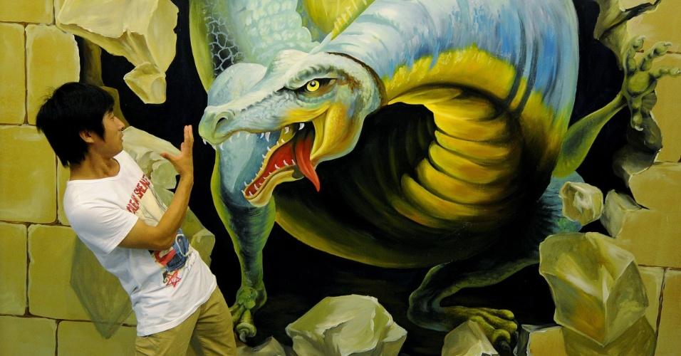 22.JUL.2012 - Jovem posa fingindo ser atacado por dragão de pintura 3D em exposição de arte tridimensional, em Hefei, província de Anhui (China)