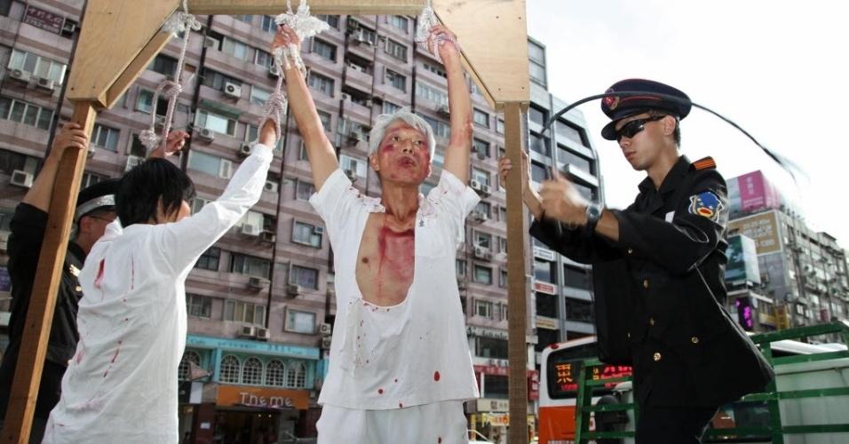 22.jul.2012 - Membros da seita Falungong simulam tortura da polícia chinesa durante protesto realizado em Taipei, Taiwan. A manifestação marca o 13 º aniversário da perseguição dos membros da Falungong, que resultou na execução de 3.600 pessoas